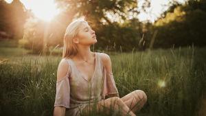 En kvinna i gräset med solnedgång som bakgrund.