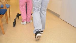 En fysioterapeut hjälper en äldre att gå.