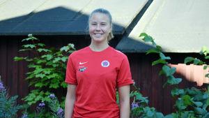 Porträttbild på Ida Adamsson i röd t-skjorta. Hon ler på bilden.