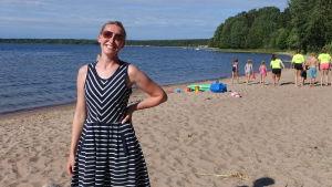 Sofia Stolt står på en sandstrand med simskoledeltagare i bakgrunden.