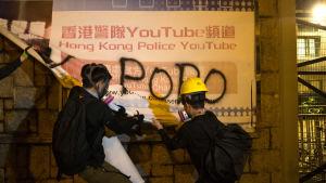 Demokratiaktivister river ner polisens annons vid en metrostation i Hongkong