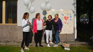 Fyra kvinnor står med ballonger i händerna.
