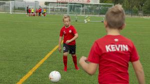 Jalkapalloa harrastava William Haapanen treenaa kaverinsa Kevin Eroman kanssa Espoonlahden urheilupuiston kentällä.