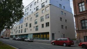 Bostadshus i Vasa centrum. Huset har en beige fasad. På gatan utanför står bilar parkerade.