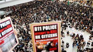 Demonstranter samlades på Hongkongs internationella flygplats på måndagen. En del bar på skyltar där polisen beskylls för att försöka döda medborgare i Hongkong.