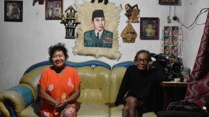 En kvinna och en man sitter på sin soffa. Ovanför soffan hänger ett porträtt på Sukarno.