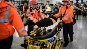 skadad man förs bort av ambulanspersonal.