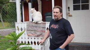 En man står på en trappa i svart t-skorta. Han heter Johan Holmberg. Bredvid honom sitter en vit katt på ett staket.