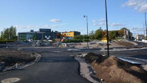 En byggarbetsplats bestående av asfalterade vägar och en stor sandplan.