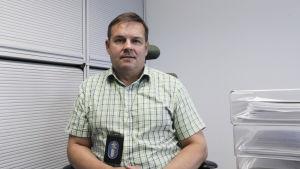 En man med en rutig grön skjorta och ett polisemblem sitter på en stor i ett kontor. Han ser in i kameran och ser allvarlig ut.
