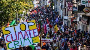 """Demonstration mot G7-länderna i Frankriket. På bilden syns ett stor plakat där det står """"Stop climate crime"""" och ett folkhav med flaggor."""