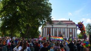 Stor folkmassa står på Lilltorget i Åbo, flera regnbågsflaggor syns i bakgrunden.