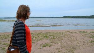 En kvinna står på en badstrand och tittar ut mot vattnet.