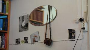 En vägg fylld med fotografier, en rund spegel och en gammal kamera som hänger från spegeln.