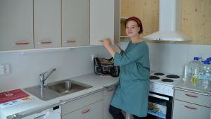 En kvinna står i ett kök och öppnar två köksskåpsdörrar.