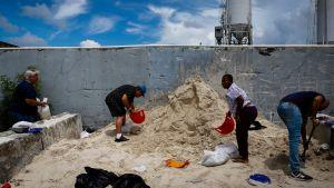 Människor i Florida samlar sand i säckar för att förebygga översvämningar inför orkanen Dorians ankomst.