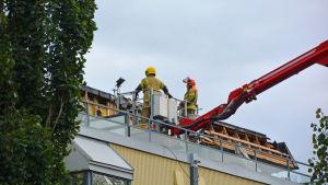 Två brandmän på det brandskadade taket.