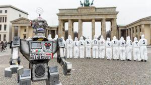 En robot i förgrunden och aktivister i bakgrunden som demonstrerar mot mördarrobotar framför Brandenburger Tor i Berlin.