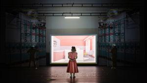 Kuvan etualalla on vaaleanpunaiseen leninkiin pukeutunut nainen selin kameraan. Hän katsoo lasilaatikkoon, johon on rakennettu pinkkivalkoinen kahvila. Hämärässä lasilaatikon ulkopuolella seisoo työmiehiä kypärät päässään, rakennustelineiden lomassa.