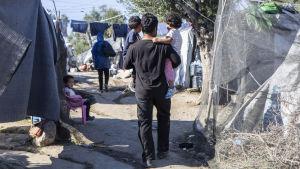 En man bärande på ett barn går genom tältby utanför flyktinglägret Moria på Lesbos.