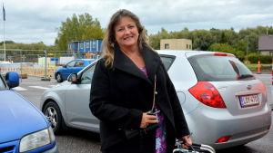 kvinna i svart höstjacka står bland bilar på en parkeringsplats, byggarbeten pågår i bakgrunden