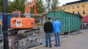 Två personer följer med när en byggnad rivs.