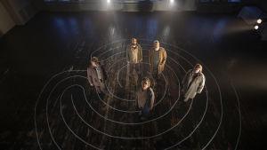 Fem skådespelare i masker står på ett mörkt golv. På golvet har ett labyrintmönster ritats.