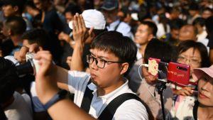 En man fotograferar med sin telefon under Kinas 70 års jubileum.