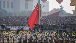 Kinas nationaldag 70 år firas, i förgrunden ses en blåsorkester och åskådare i bakgrunden.