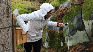 En kvinna i vit regnrock håller i en ficklampa och lyser in i en liten grotta.
