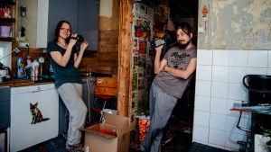 Muuttopäiväkirjat-ohjelman Taija ja Antti seisovat sotkuisessa keittiössä videokamerat käsissään.