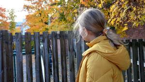 En flicka i en gul jacka tittar bort mot horisonten.