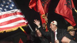 Albin Kurti ses i mitten av bilden, omgiven av flaggor och personer som firar.