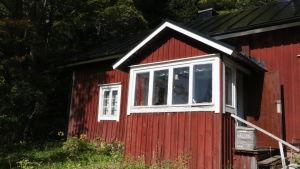 Ett rött stockhus med en veranda med stora glasfönster.