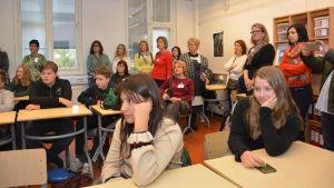 En massa elver sitter vid bord i ett klassrum.
