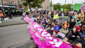 Klimataktivister protesterar genom att blockera en gata i Amsterdam.