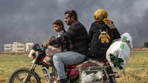 En syrisk familj flydde från staden Ras al-Ain på en motorcykel på söndagen. Röken bakom dem kommer från brinnande bildäck. Man har satt eld på dem för att skymma sikten för turkiskt krigsflyg.