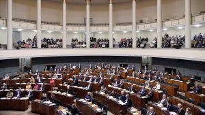 Riksdagsledamöter sitter i riksdagens plenisal, journalister på pressläktaren ovanför.