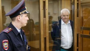 En uniformbeklädd polis står bredvid en rättsbur där Frode Berg står.
