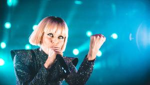 Vesala laulaa nyrkki pystyssä ja katsoo yleisöön.
