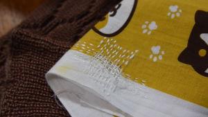En japansk handduk med animerat tryck som föreställer katter och spår av tassar. Handduken är lagad med sashiko-stygn.