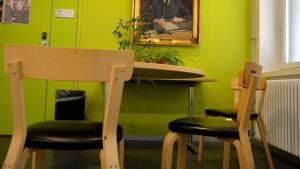 bord och stolar och en tavla i ett grönt rum