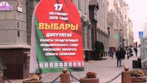 En stor valaffisch i grönt och rött med vit text i kyrilliska bokstäver står på en gata med stenhus i ljus sten. Också gatan är i vit sten.