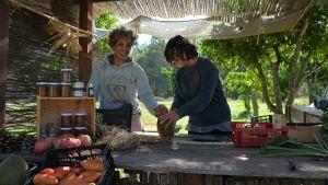Två leende kvinnor står och lagar mat under ett tak gjort av strå.