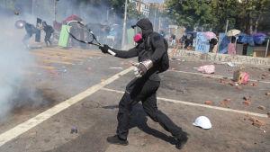 En demonstrant som skjuter i väg något med en tennisklubba.