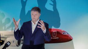 En bild på koncernchef Jacob Schram där han håller händerna framför sig och visar någonting.