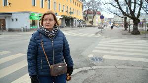 En kvinna står framför en korsning inne i en stad.