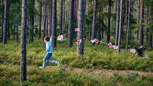 Pojke springer genom barrskog med tygstycken på ett snöre.