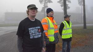 Tre män står på rad ute i dimman.