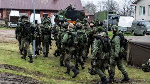 Soldater framför ett militärfordon.